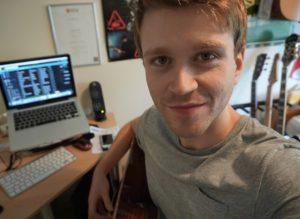 Richard Hunt sat at a desk, holding a guitar.