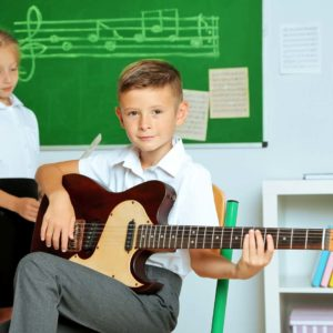 boy and girl in a classroom boy playing the guitar and g