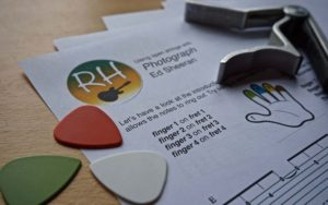 plectrums and capo resting on a worksheet.