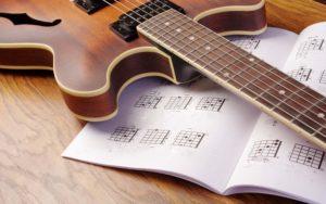 guitar lying on a guitar music book