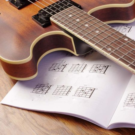 guitar lying on a guitar music book