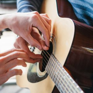 teacher helping guitar pupil to place fingers on the guitar