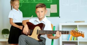 boy and girl having a guitar lesson at school